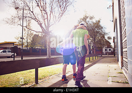 Boys carrying skateboards with arms around each other - Stock Photo
