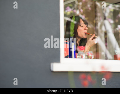 Mature woman at house window tasting food from spatula - Stock Photo