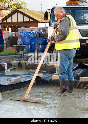 self building house, pouring floor slab, man roughly levelling concrete manually - Stock Photo