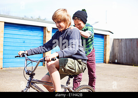 Boy giving friend a ride on back of bike - Stock Photo