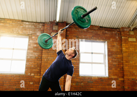Man lifting barbell with one hand - Stock Photo