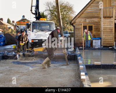 self building house, man pouring floor slab, directing concrete pump - Stock Photo