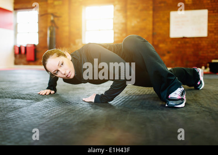 Woman doing stretching exercise in gym - Stock Photo