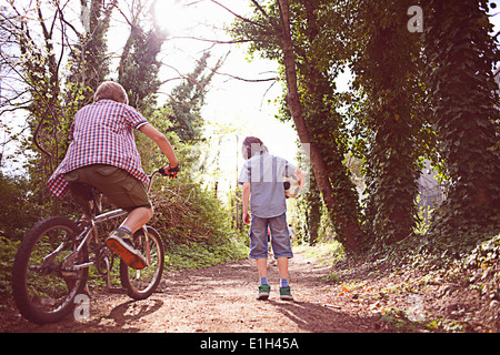 Boy on bike with friend on forest path - Stock Photo