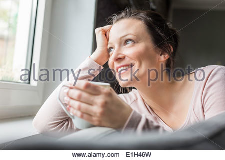 Mid adult woman looking out of window with coffee - Stock Photo