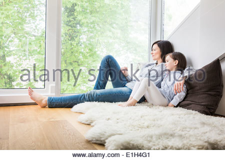 Mother and daughter sitting on fur rug at home - Stock Photo