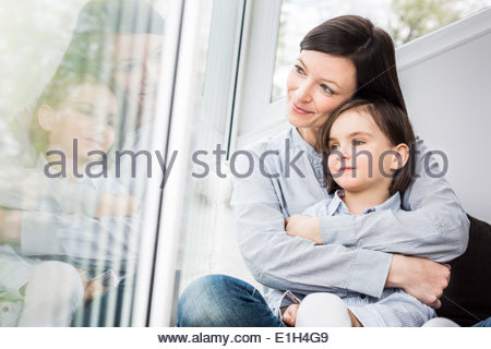 Mother and daughter hugging by window - Stock Photo