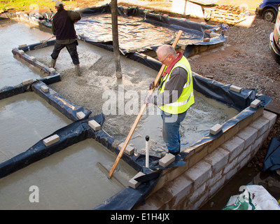 self building house, pouring floor slab, man levelling concrete by hand raking - Stock Photo