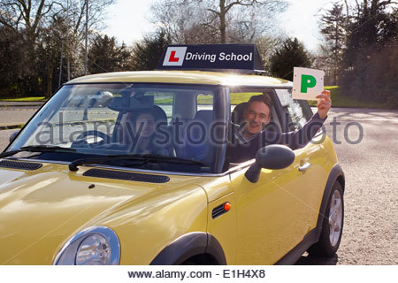 Driving instructor holding Passed Plate out of car window - Stock Photo