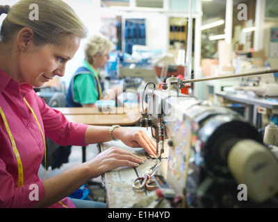 Worker sewing in clothing factory - Stock Photo