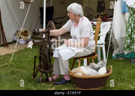 Lady using a vintage spinning wheel - Stock Photo