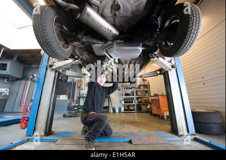 A mechanic is checking the exhaust of a car who is lifted up in a repair service station. - Stock Photo