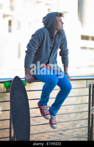 Young man gazing from riverside railings - Stock Photo