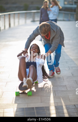 Young couple fooling around on skateboard at riverside