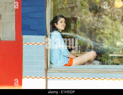 Young woman looking out of cafe window - Stock Photo