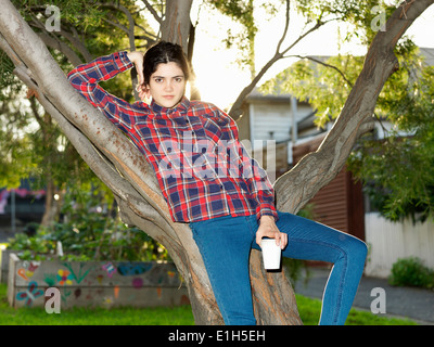 Portrait of confident young woman reclining against tree - Stock Photo