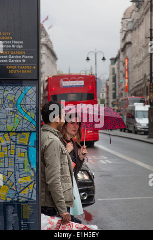 Woman holding an umbrella prepares to cross the busy Strand in London with an open-roof red double decker bus in - Stock Photo
