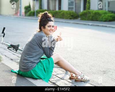 Portrait of young woman eating ice cream on sidewalk - Stock Photo
