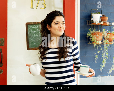 Young female waitress serving coffee outdoors - Stock Photo