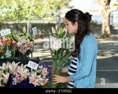 Young woman smelling cut flowers on street - Stock Photo