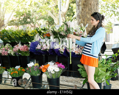 Young woman choosing cut flowers on street - Stock Photo