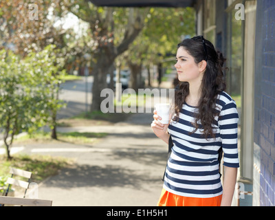 Young woman with takeaway coffee waiting on street - Stock Photo