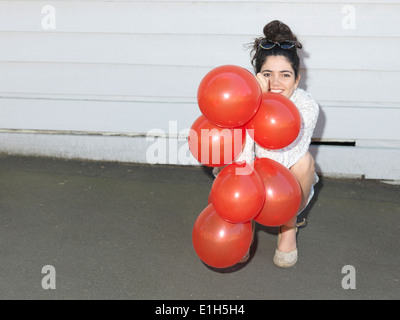 Portrait of young woman crouching with a bunch of balloons - Stock Photo