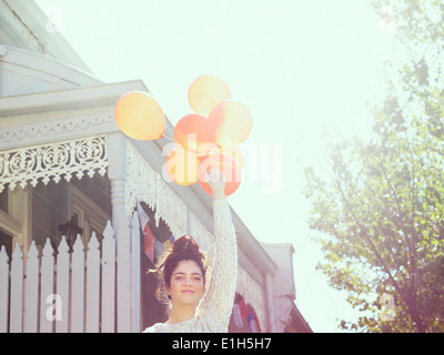 Portrait of young woman holding up a bunch of balloons - Stock Photo
