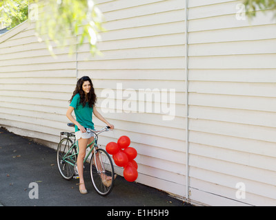 Portrait of young woman with bicycle and a bunch of balloons - Stock Photo