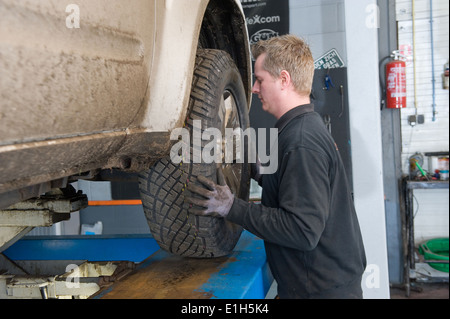 A mechanic is changing the wheel of a lifted car on a bridge in a garage. - Stock Photo