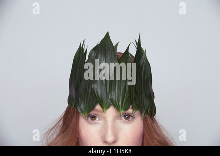 Young woman wearing crown of leaves - Stock Photo