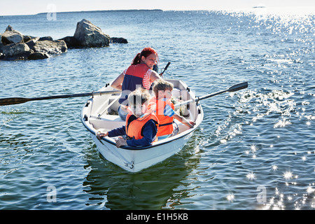 Mother and two young sons in rowing boat on lake, Gavle, Sweden - Stock Photo