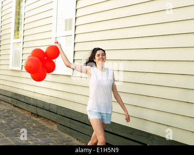 Young woman walking along alley with bunch of balloons - Stock Photo