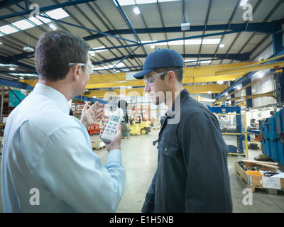 Office and factory worker checking sound volume in factory - Stock Photo
