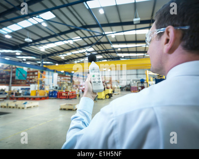 Office worker checking sound volume in factory - Stock Photo