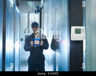 Proud factory worker showing energy saving on digital tablet in factory, portrait - Stock Photo