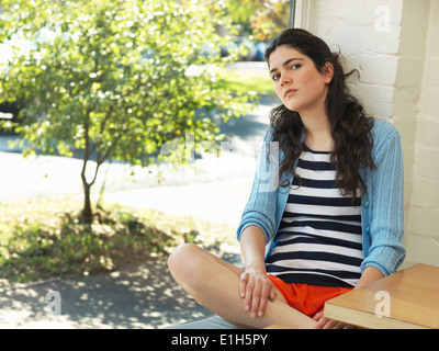 Portrait of sullen young woman leaning against wall - Stock Photo