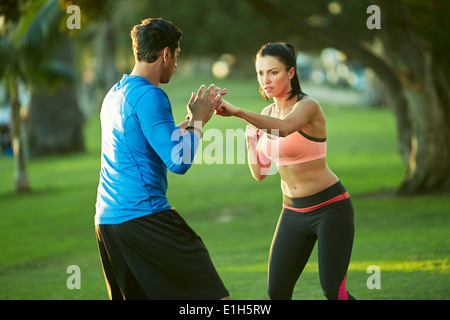 Man and woman in park boxing - Stock Photo