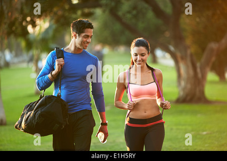 Man and woman wearing sports clothes walking through park - Stock Photo
