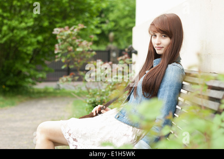 Portrait of young woman sitting on garden bench - Stock Photo