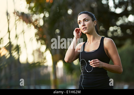 Mid adult woman putting in earphones - Stock Photo