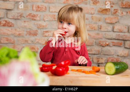 Two year old girl in kitchen eating raw vegetables - Stock Photo