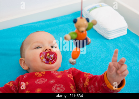 Contented 7 month old baby girl playing with dangling teddybear - Stock Photo