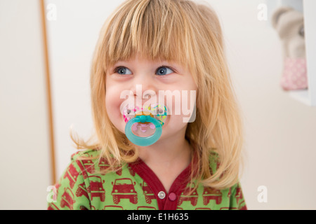 Portrait of happy 2 year old girl with pacifier - Stock Photo