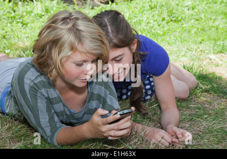 Teenage girls lying on grass, using smartphone - Stock Photo