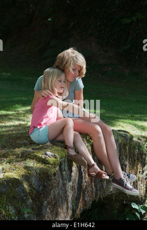 Sisters sitting in garden - Stock Photo