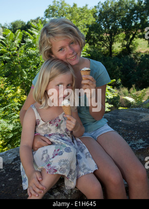 Sisters sitting in garden eating ice cream - Stock Photo