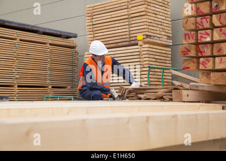 Woodworker sorting wooden planks in timber yard - Stock Photo