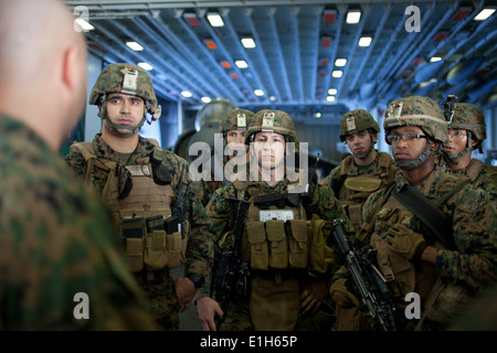 U.S. Marines with India Company, Battalion Landing Team, 3rd Battalion, 1st Marine Regiment, listen to directions - Stock Photo