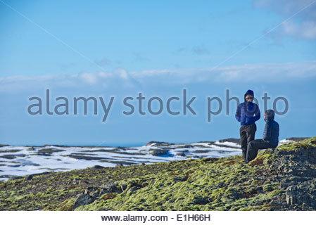 Young hiking couple taking a break at Breidamerkurjokull, Vatnajokull National Park, Iceland - Stock Photo